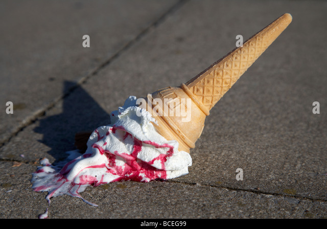 ice cream cone dropped onto pavement - Stock Image