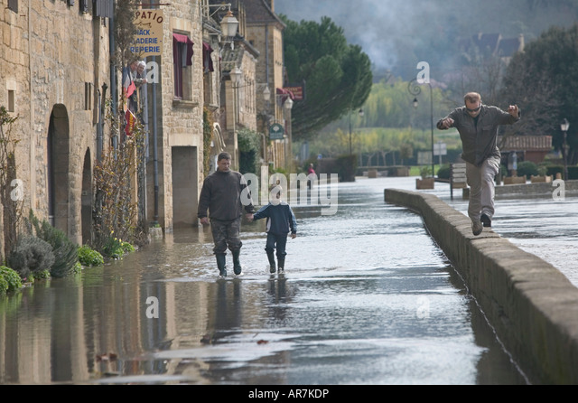 River Dordogne overflows into the main street of an adjacent village following a period of heavy and persistent - Stock Image