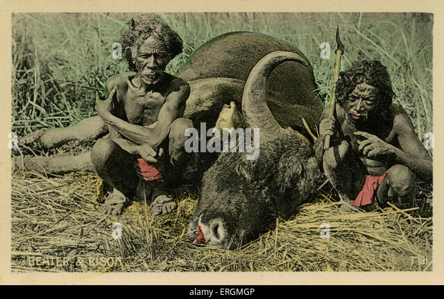Two Indian farmers by a dead bison. Colourised photograph taken early