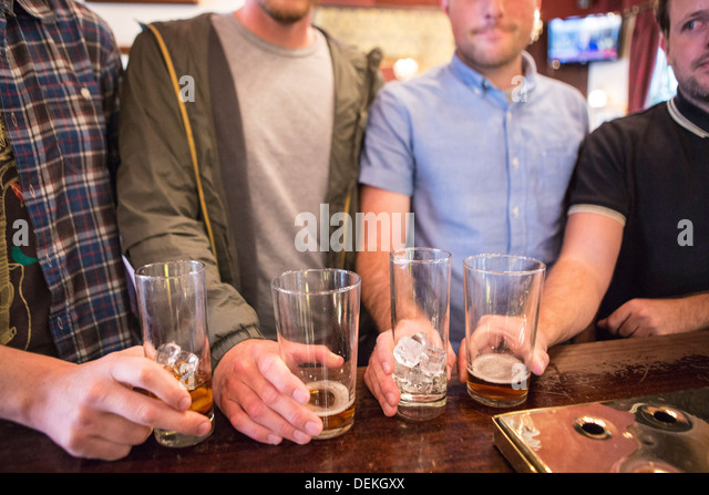 Four white British men line up their pint glasses on a bar in an English pub in London, United Kingdom. - Stock Image