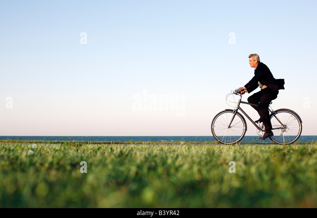 Man in suit rides bicycle along Chicago lakefront at dusk - Stock Image