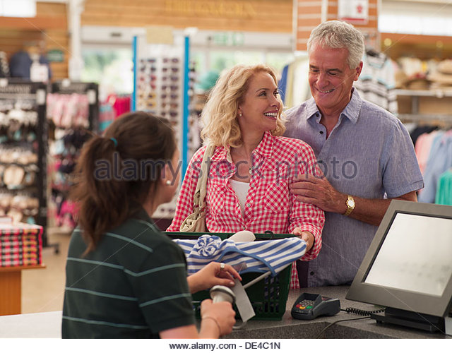 Cashier scanning coupleÂ's purchases in store - Stock Image