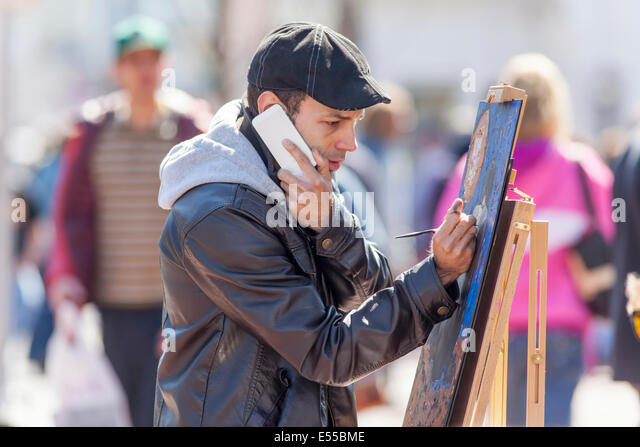 A painter artist paints a picture on a city street. - Stock Image