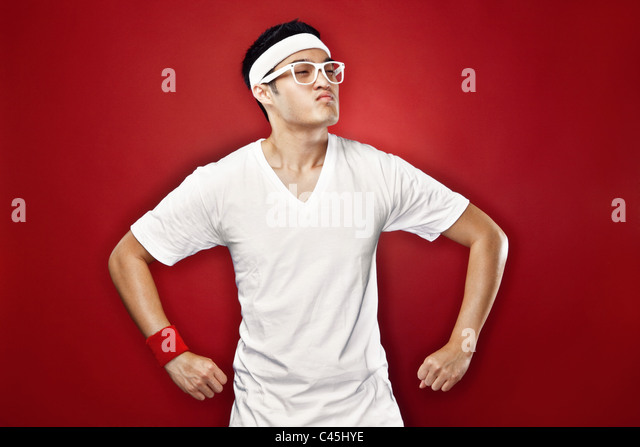 Studio portrait of Asian male teenager doing a superhero pose in white athletic gear & nerdy glasses against - Stock Image