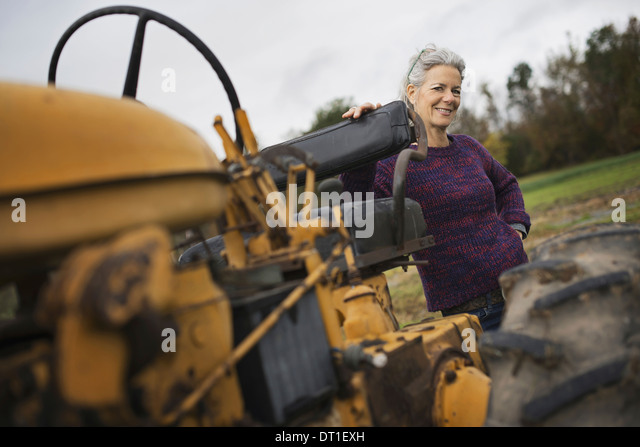 Organic Farmer at Work A woman by a tractor - Stock Image