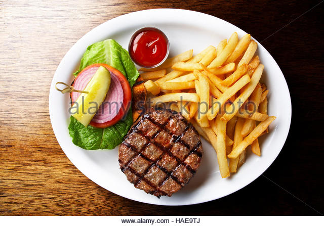 Grilled American hamburger with fries,greens,onions and,pickles - Stock Image