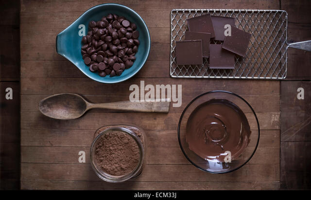 Top down view of chocolate baking supplies laid out on a rustic wood surface with antique props. - Stock Image
