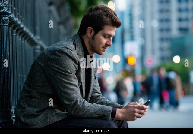 Young man waiting on city street, Toronto, Ontario, Canada - Stock Image