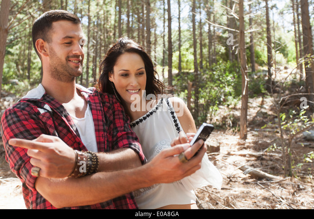 Young couple in forest, man pointing - Stock-Bilder