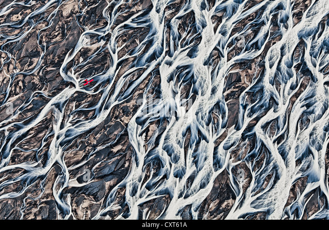 Aerial view, a red single-engine lightweight airplane flying over the flow structures of the melt water branching - Stock Image