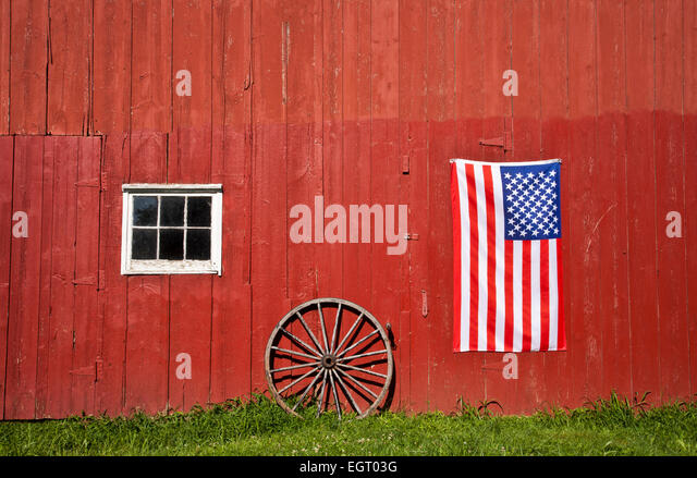 Historical red barn close with the US flag and an antique wagon wheel on a farm, Middlesex county, Monroe Twp., - Stock Image