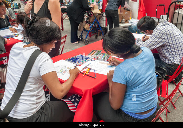 Visitors to Times Square in New York on Tuesday, August 2, 2016 take advantage of free coloring books and supplies - Stock Image