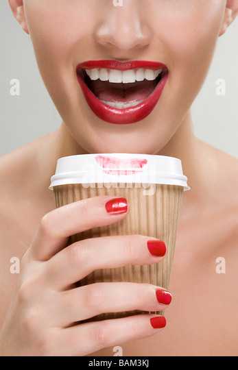 Woman drinking coffee from a paper cup - Stock Image
