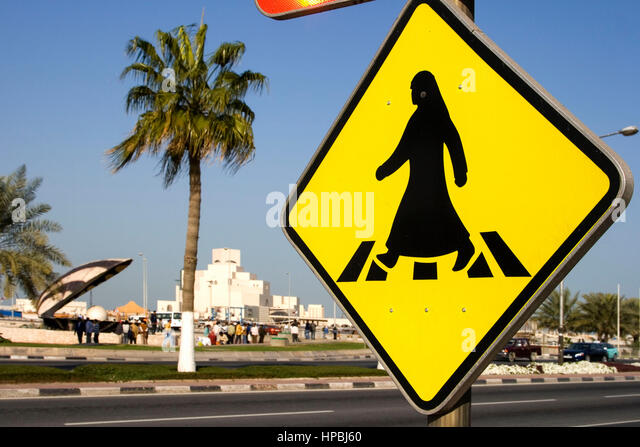 Qatar Doha arabian sign for crosswalk at the al corniche street , in the background  Museum of islamic art and the - Stock Image