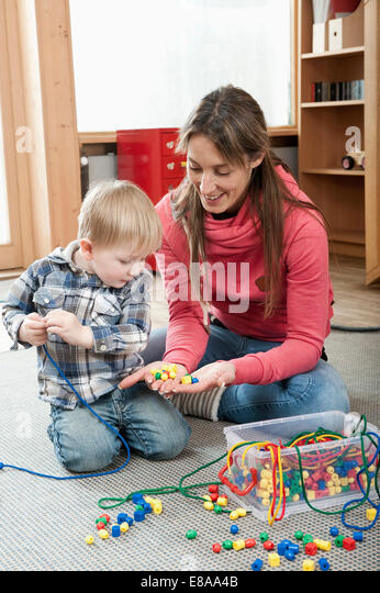 Female educator offering little boy wooden perls for making a necklace - Stock Image