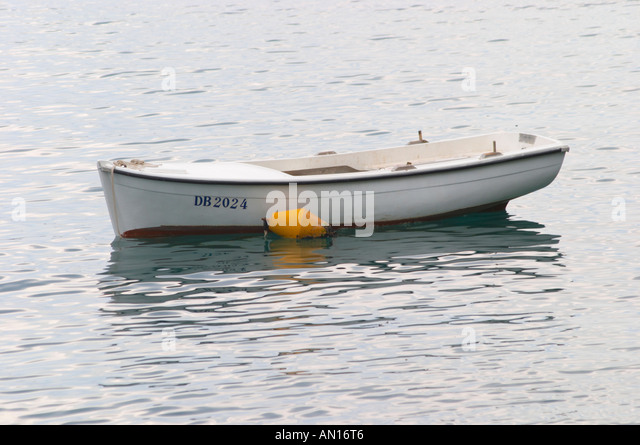 A white rowing boat moored by a yellow buoy Uvala Sumartin bay between Babin Kuk and Lapad peninsulas. Dubrovnik, - Stock Image