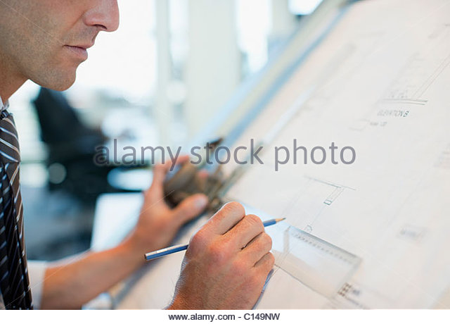 Businessman drawing on drafting table in office - Stock Image
