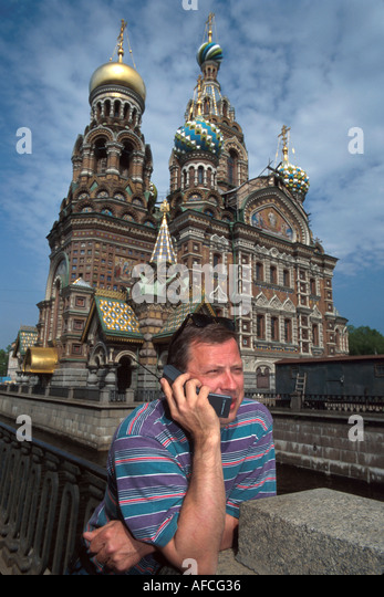 Russia former Soviet Union St. Petersburg businessman cell phone Church on Savior's Blood Czar Alexander II - Stock Image