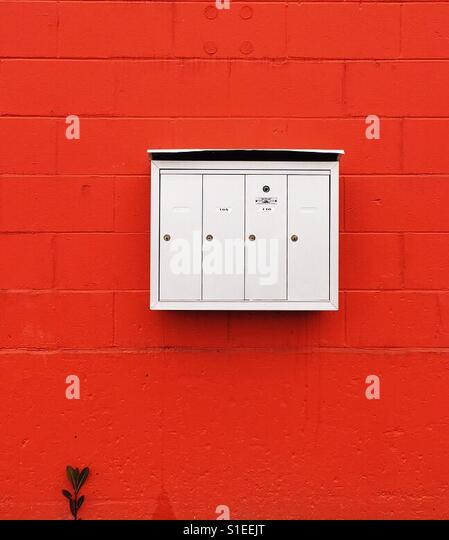 Mailboxes against a bold coloured orange/red wall - Stock Image
