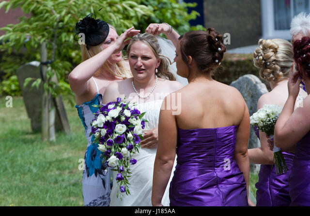 Bride has her veil adjusted before her wedding - Stock Image
