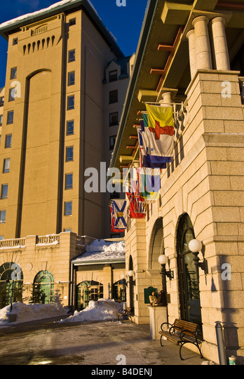 Fairmont Chateau Lake Louise with flags of nations flying over entrance on bright sunny winter day - Stock Image