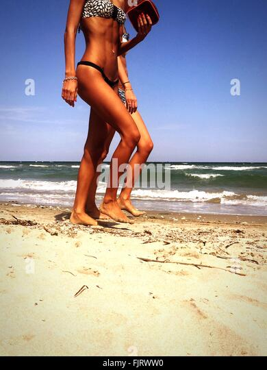 Two Women Walking On Beach - Stock Image