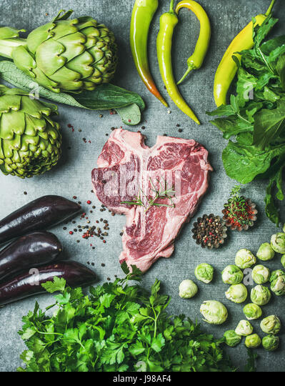Raw beef uncooked t-bone steak with green vegetables and spices - Stock Image