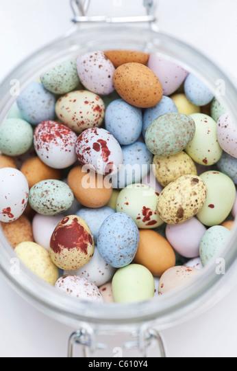 Chocolate mini eggs in a glass jar - Stock Image
