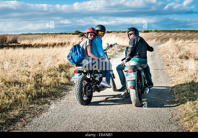 Rear view of three friends on motorcycles on rural road, Cagliari, Sardinia, Italy - Stock Image