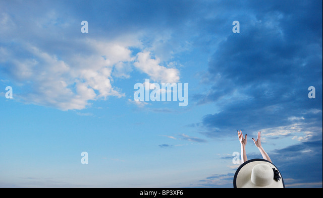 Woman wearing hat reaches her arms up into the sky - Stock Image