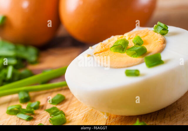 Half of boiled egg  prepared on cutting board with sliced chive and two whole eggs in background - Stock Image