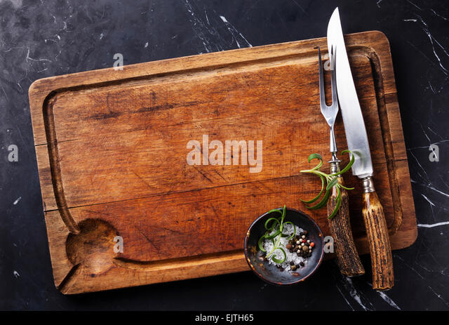 Chopping cutting board, seasonings and rosemary with fork and knife carving set on dark marble background - Stock Image