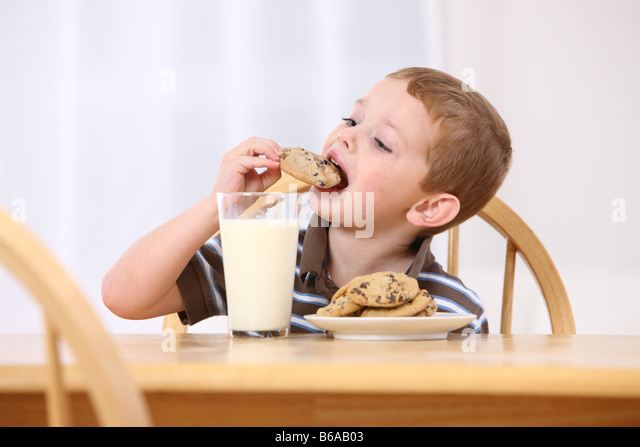 Young boy eating chocolate chip cookies and milk - Stock-Bilder