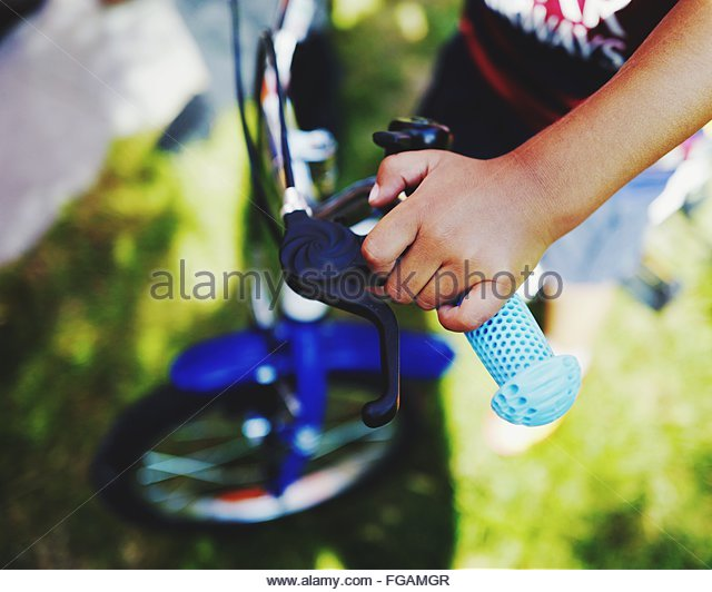 Low Section Of Child Hand On Bicycle Handlebar - Stock-Bilder