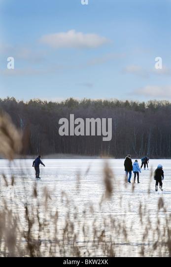 group of people skating on lake - Stock Image