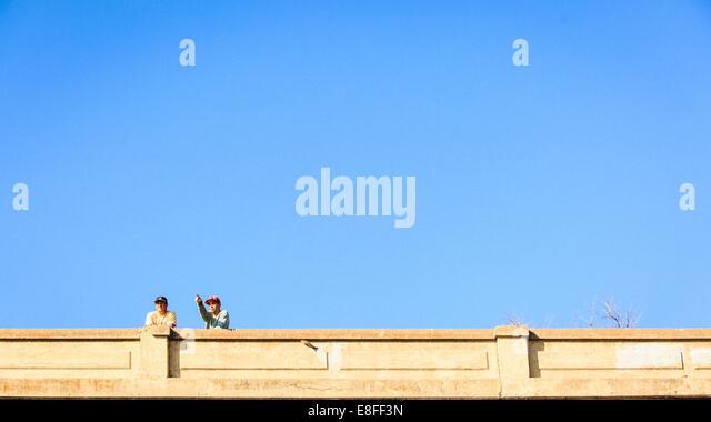 Two men standing on bridge - Stock Image