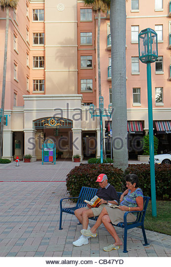 Boca Raton Florida Mizner Park Plaza Real shopping dining palm trees pink building public bench woman man couple - Stock Image