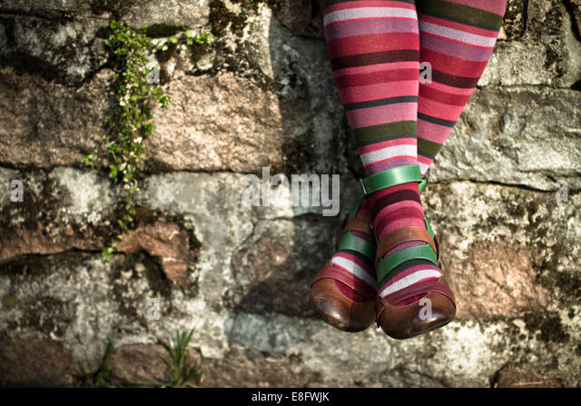Italy, Lombardy, Milan, Woman wearing striped socks while sitting on wall - Stock Image