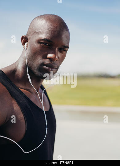 Image of handsome young man wearing earphones looking at camera. African male model outdoors. - Stock Image