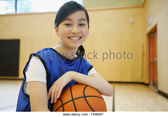 Female, middle school student posing with basketball. - Stock Image