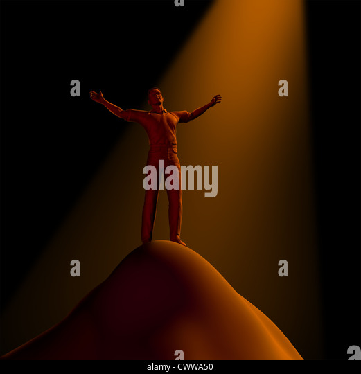 Faith and religion represented by a man on a mountain with his arms raised to the heavens in search of beleif and - Stock Image