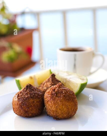 Three small pieces of kebbe, a lebanese dish with mince meat or mushrooms and lemon and coffee on the background. - Stock Image