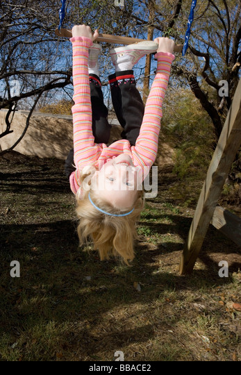 A young girl hanging upside down from a swing - Stock-Bilder