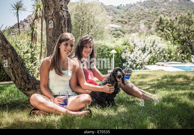 Portrait of two female friends with dog in holiday home garden, Capoterra, Sardinia, Italy - Stock-Bilder