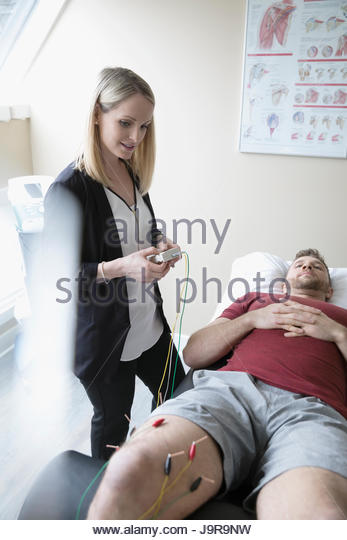 Female acupuncturist applying electric needles to knee of man on clinic examination table - Stock-Bilder