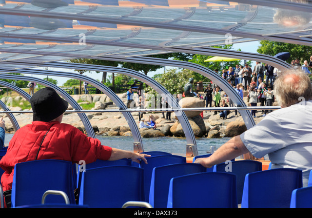 Tourists on a sightseeing boat tour looking at the Little Mermaid statue on the waterfront in Copenhagen, Zealand, - Stock Image