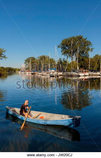 canoe canoeing Toronto Islands Park lagoon trees reflected Toronto Ontario Canada - Stock Image