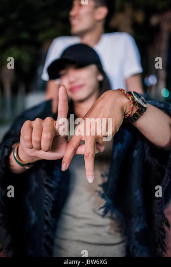 Portrait of young woman making LA hand gesture outside Los Angeles County Museum of Art at night - Stock-Bilder