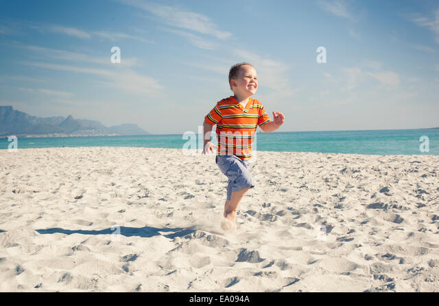 Boy running on beach, Cape Town, Western Cape, South Africa - Stock Image