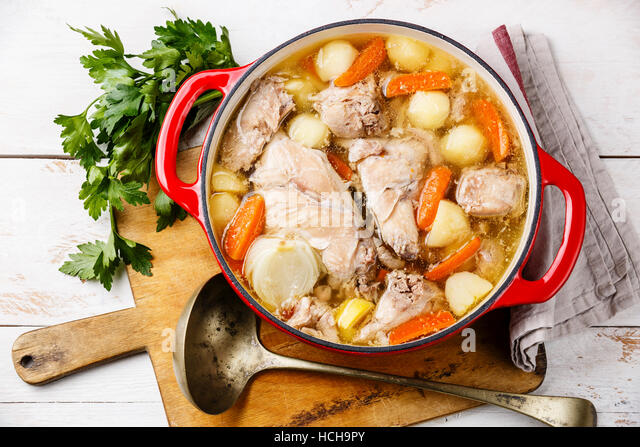 Stewed rabbit with potatoes and carrot in cast iron pot on rustic wooden table background - Stock Image